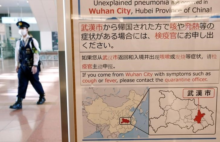 Foto de archivo de un policía con una mascarilla pasando cerca de un cartel que informa sobre el brote de coronavirus en Wuhan, China, en el aeropuerto de Haneda en Tokio. Ene 20, 2020. REUTERS/Kim Kyung-Hoon