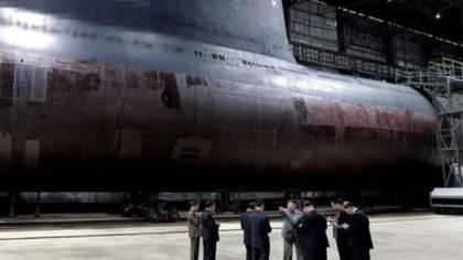 Kim Jong-un visita el astillero Shinpo. Detrás de él, lo que se cree podría ser el nuevo submarino de Corea del Norte (CSIS/Airbus)