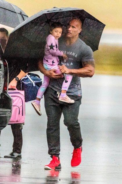 """Dwayne Johnson -popularmente conocido como """"La Roca""""- fue visto junto a su esposa, Lauren Hashian, y sus hijos y la mascota de la familia bajando de su avión privado en Atlanta, Georgia. El actor protegió a una de sus hijas de la lluvia con un enorme paraguas mientras caminaba por la pista con la niña en brazos"""
