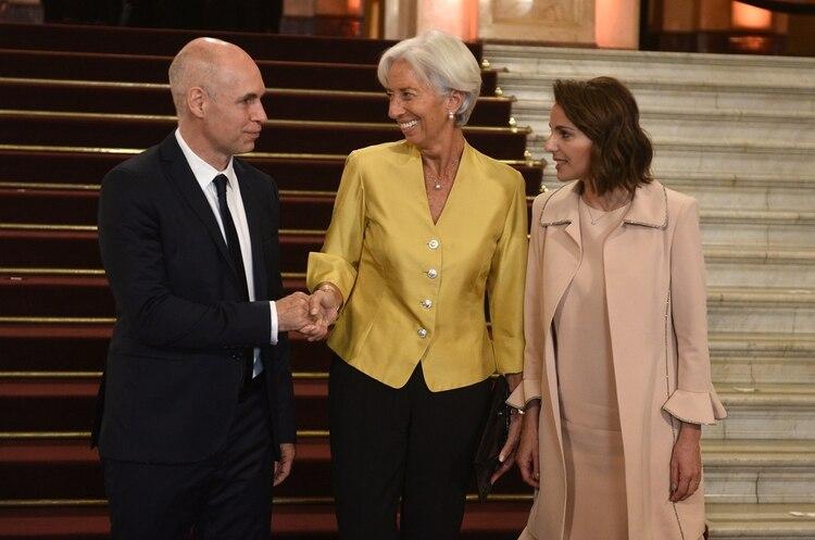 Christine Lagarde participó de la gala del Colón con un look masculino de dos piezas. Una chaqueta en color mostaza con botones plateados completando el look con pantalón recto negro y sobre a tono (Presidencia)