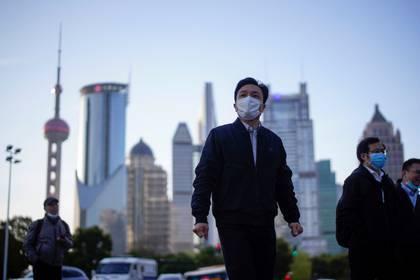 Personas con máscaras faciales protectoras tras el brote de coronavirus (COVID-19), en el distrito financiero de Lujiazui en Shanghai, China, este 19 de marzo de 2020 (Reuters)