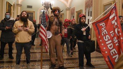 La policía del Capitolio trata de impedir que los partidarios del presidente Trump, liderados por Jacob Anthony Chansley, entren en el Capitolio el 6 de enero de 2021 (Foto de Saul LOEB / AFP)