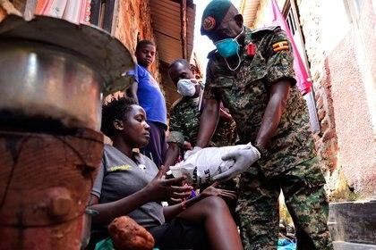 Una mujer recibe alimentos durante un ejercicio de distribución del Gobierno a los civiles afectados por la cuarentena, como parte de las medidas para prevenir la propagación del coronavirus, en Kampala, Uganda (Reuters/ Abubaker Lubowa)
