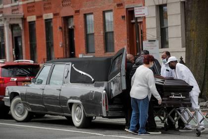 Trabajadores de una funeraria colocan el cuerpo de un fallecido durante un funeral durante el brote de la enfermedad por coronavirus en Brooklyn, Nueva York.