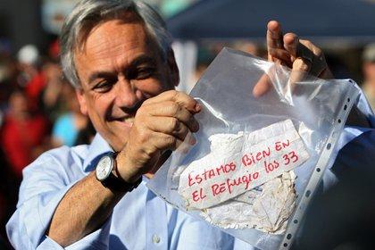 """El presidente chileno Sebastián Piñera muestra el icónico mensaje en el que los mineros confirmaron que todos se encontraban con vida: """"Estamos bien en el refugio los 33"""", indicó el mensaje escrito por José Ojeda (AFP)"""