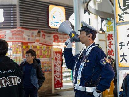 Un policía trata de mantener el orden en una calle en Tokio (Shutterstock)