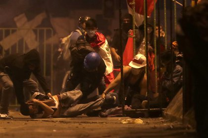 Un manifestante cae herido en el piso mientra otros tratan de ayudarlo durante de las protestas contra el nuevo presidente de Perú