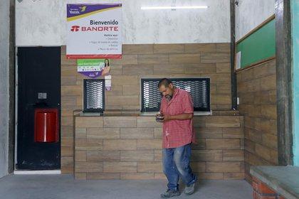 Fotografía del 7 de febrero de 2020 que muestra a un hombre que retira dinero en una casa de cambio de divisas en el municipio de Tepeojuma. Tepeojuma, un municipio de unos 8.500 habitantes en el centro de México. EFE/Hilda Ríos/Archivo