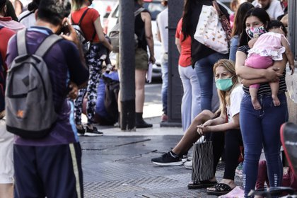 Varias personas hacen fila para aplicar a opciones de trabajo, ante cada cada búsqueda de empresas (EFE)