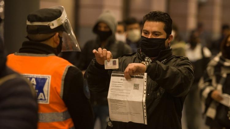 Un pasajero muestra su permiso para poder abordar el transporte público (Adrián Escandar)