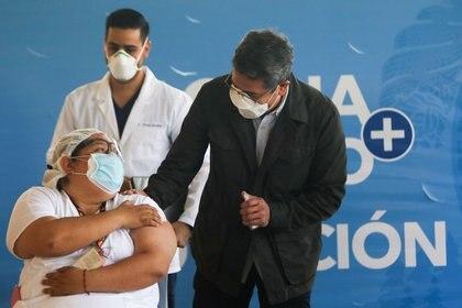 La trabajadora de salud Soraya Ortega habla con el presidente hondureño Juan Orlando Hernández luego de recibir una dosis de la vacuna contra la enfermedad del coronavirus Moderna (COVID-19) en el Hospital María, en Tegucigalpa, Honduras, el 25 de febrero de 2021. REUTERS/Stringer NO RESALES. NO ARCHIVES