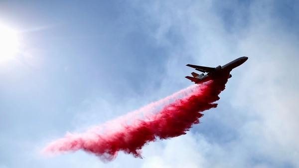 Una nave de los bomberos arroja químicos que frenan el avance de las llamas (Reuters)