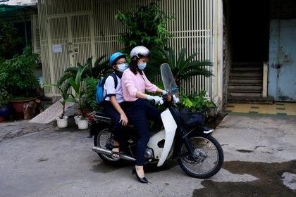 Una madre se prepara para llevar a su hija al colegio en Vietnam