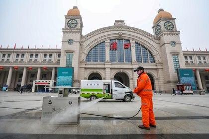 Un empleado del municipio de Wuhan, protegido con un barbijo, higieniza la zona cercana a la estación central de trenes, clausurada por el brote de coronavirus (Reuters)