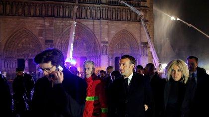 El presidente francés Emmanuel Macron junto a su esposa Brigitte camina afuera de la catedral de Notre Dame en París, donde los bomberos intentan preservar la estructura (Foto: REUTERS)