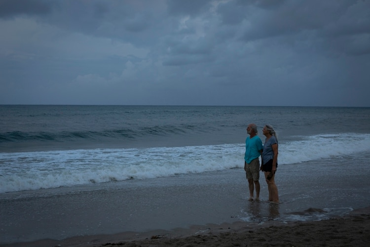 Dos personas observan el mar en Lantana Beach, Florida, antes de la llegada del huracán Dorian (Photo by Eva Marie UZCATEGUI / AFP)