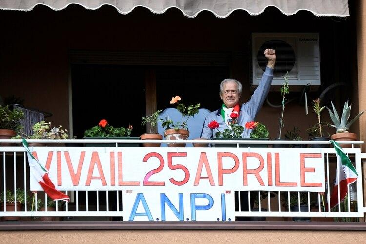 Un hombre celebra el Día de la Liberación en el balcón de un apartamento en Milán