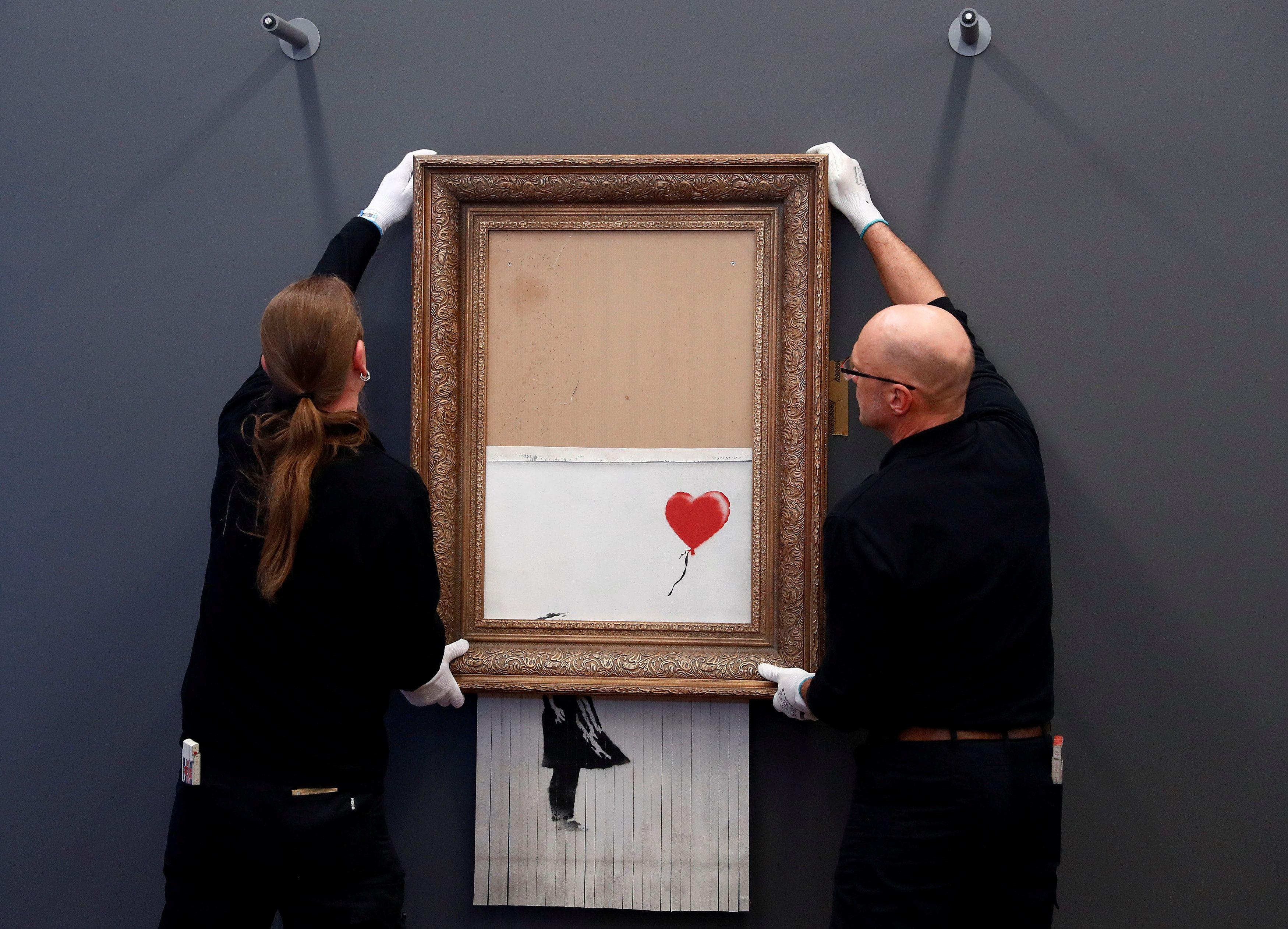 """Empleados de la casa de remates Sotheby en Londres sostienen la obra de Banksy conocida originalmente como """"Niña con globo"""" que se retituló """"El amor está en el tacho"""" al destruirse tras su venta y convertirse en la primera pieza en la historia creada en vivo durante una subasta el 5 de octubre de 2018"""