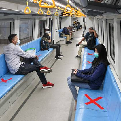"""People sit on designated areas decided by red cross marks to ensure social distancing inside a light rapid transit train in Palembang, South Sumatra on March 20, 2020, amid concerns of the COVID-19 coronavirus outbreak. (Photo by Abdul QODIR / AFP) / """"The erroneous mention[s] appearing in the metadata of this photo has been modified in AFP systems in the following manner: [byline as Abdul Qodir] instead of [byline as Berto]. Please immediately remove the erroneous mention[s] from all your online services and delete it (them) from your servers. If you have been authorized by AFP to distribute it (them) to third parties, please ensure that the same actions are carried out by them. Failure to promptly comply with these instructions will entail liability on your part for any continued or post notification usage. Therefore we thank you very much for all your attention and prompt action. We are sorry for the inconvenience this notification may cause and remain at your disposal for any further information you may require."""""""