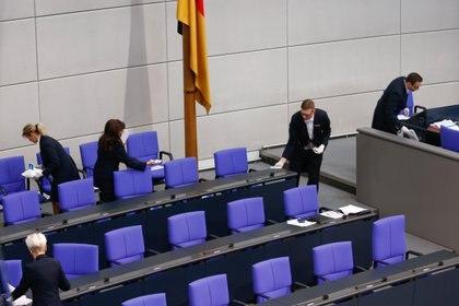 Miembros del parlamento desinfectan y limpian los asientos de la cámara baja en Alemania (REUTERS/Michele Tantussi)