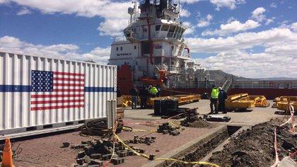 La bandera de los Estados Unidos y los operarios trabajando para acelerar la búsqueda del ARA San Juan