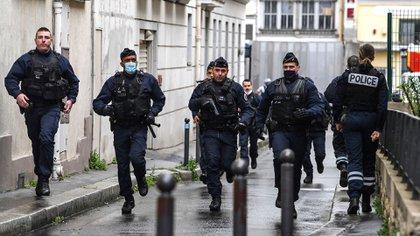 Agentes de la policía francesa se apresuran a acudir al lugar de los hechos después de que se produjeran heridos cerca de las antiguas oficinas de la revista satírica francesa Charlie Hebdo (Foto de Alain JOCARD / AFP)