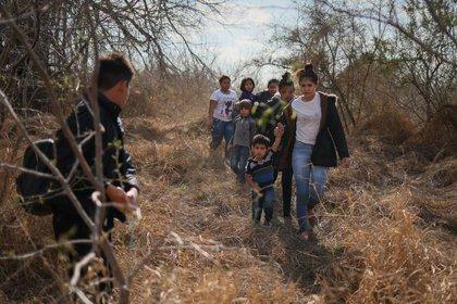FOTO DE ARCHIVO. Familias migrantes y niños de Centroamérica salen de la espesa maleza después de cruzar el Río Grande hacia Estados Unidos desde México, en Penitas, Texas, EEUU. 6 de marzo de 2021. REUTERS/Adrees Latif