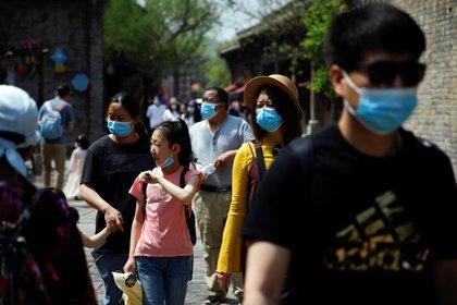 Personas con máscaras visitan la Ciudad del Agua de Gubei en el primer día de los cinco días de fiesta del Día del Trabajo, después del brote de la enfermedad coronavirus (COVID-19), en las afueras de Beijing, China, el 1 de mayo de 2020 (REUTERS/Carlos Garcia Rawlins)