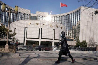 Mujer con una mascarilla frente a la sede del Banco Popular de China, el banco central, en Pekín, China, 3 febrero 2020. REUTERS/Jason Lee