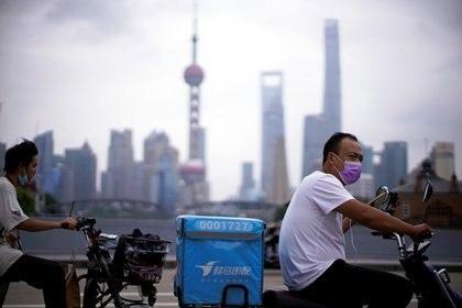 Trabajadores de delivery en Shanghai, China (REUTERS/Aly Song)