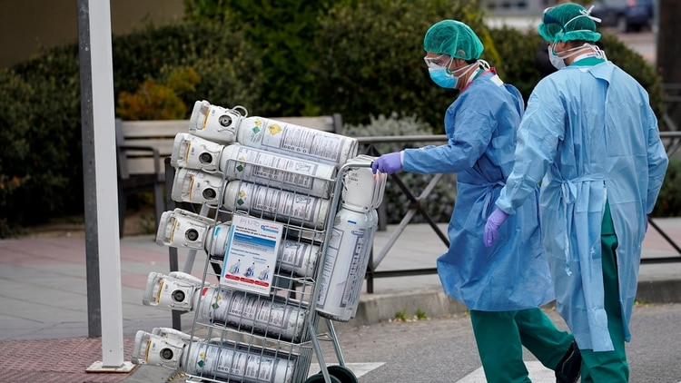 FILE PHOTO: Healthcare workers wearing protective face masks bring oxygen bottles to the emergency unit at 12 de Octubre Hospital, amid the coronavirus disease (COVID-19) outbreak in Madrid, Spain March 30, 2020. REUTERS/Juan Medina/File Photo