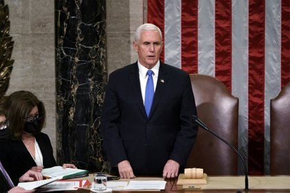 FILE PHOTO: U.S. Vice President Mike Pence reads the final certification of Electoral College votes cast in November's presidential election during a joint session of Congress after working through the night, at the Capitol in Washington, U.S., January 7, 2021. Protesters loyal to President Donald Trump stormed the Capitol Wednesday, disrupting the process. J. Scott Applewhite/Pool via REUTERS/File Photo