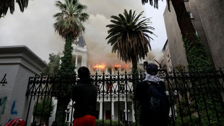 Encapuchados observan cómo se incendia una sede de la Universidad Pedro de Valdivia (Reuters)