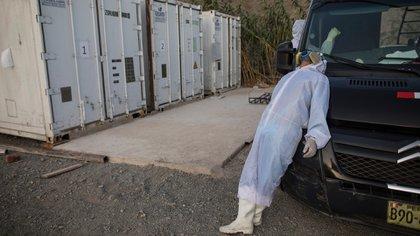 El venezolano Ángelo Aza se toma un descanso en su trabajo de trasladar los cuerpos de supuestas víctimas del coronavirus, tendido sobre un auto de la funeraria Piedrangel, junto a contenedores de mercancías habilitados para mantener los cadáveres refrigerados, en un hospital público de Lima, Perú, el 11 de mayo de 2020. (AP Foto/Rodrigo Abd)