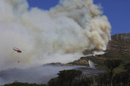 Un helicóptero arroja agua sobre el  incendio en el Rhodes Memorial en Table Mountain, Ciudad del Cabo. (Foto AP / Nardus Engelbrecht)