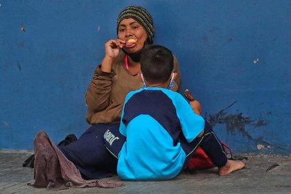 Una mujer y un niño permanecen sentados en una calle en la que piden dinero este miércoles en Tegucigalpa (Honduras). EFE/ Gustavo Amador