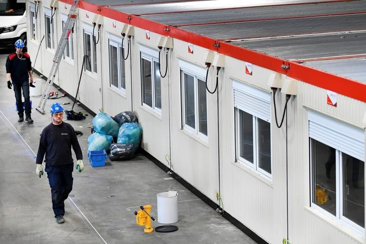 Operarios caminan cerca de las unidades dentro de la sala de conciertos Ahoy, se utiliza como hospital de emergencia en Rotterdam, el 30 de marzo de 2020. (REUTERS/Piroschka Van De Wouw)