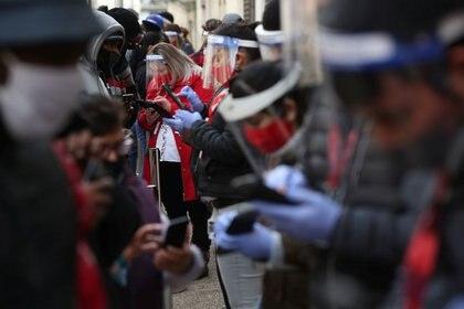 FOTO DE ARCHIVO. Trabajadores de una sucursal de una AFP (Administradoras de Fondos de Pensión), que usan protectores faciales, ayudan a sus clientes a actualizar su información personal para retirar el 10% de sus ahorros de la seguridad social, para ayudar a aliviar el dolor económico causado por el brote de la enfermedad del coronavirus (COVID-19) , luego de que el Congreso de Chile diera su aprobación mediante un proyecto de ley, en Santiago, Chile. 30 de julio de 2020. REUTERS/Iván Alvarado