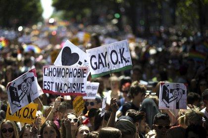 """Manifestantes en París sostienen carteles que dicen """"la homofobia es machismo"""" y """"Gay, ok"""" el 27 de junio de 2015"""