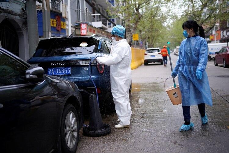 Un hombre lava un automóvil en las calles de Wuhan. (Reuters)