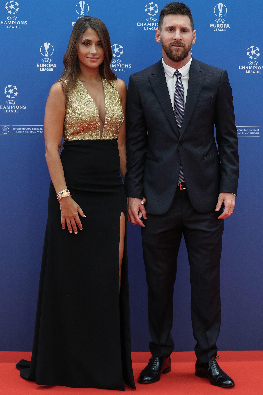 Antonela Roccuzzo con su vestido sirena en dorado y negro y Lionel Messi optó por un esmoquin azul noche(Photo by Valery HACHE / AFP)
