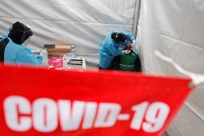 Un trabajador de la salud que usa equipo de protección personal (EPP) toma una muestra de hisopo de un hombre para obtener un resultado rápido en la prueba de la enfermedad por coronavirus (COVID-19) en Ciudad de México, México, 20 de noviembre de 2020. REUTERS / Carlos Jasso/ Foto de archivo