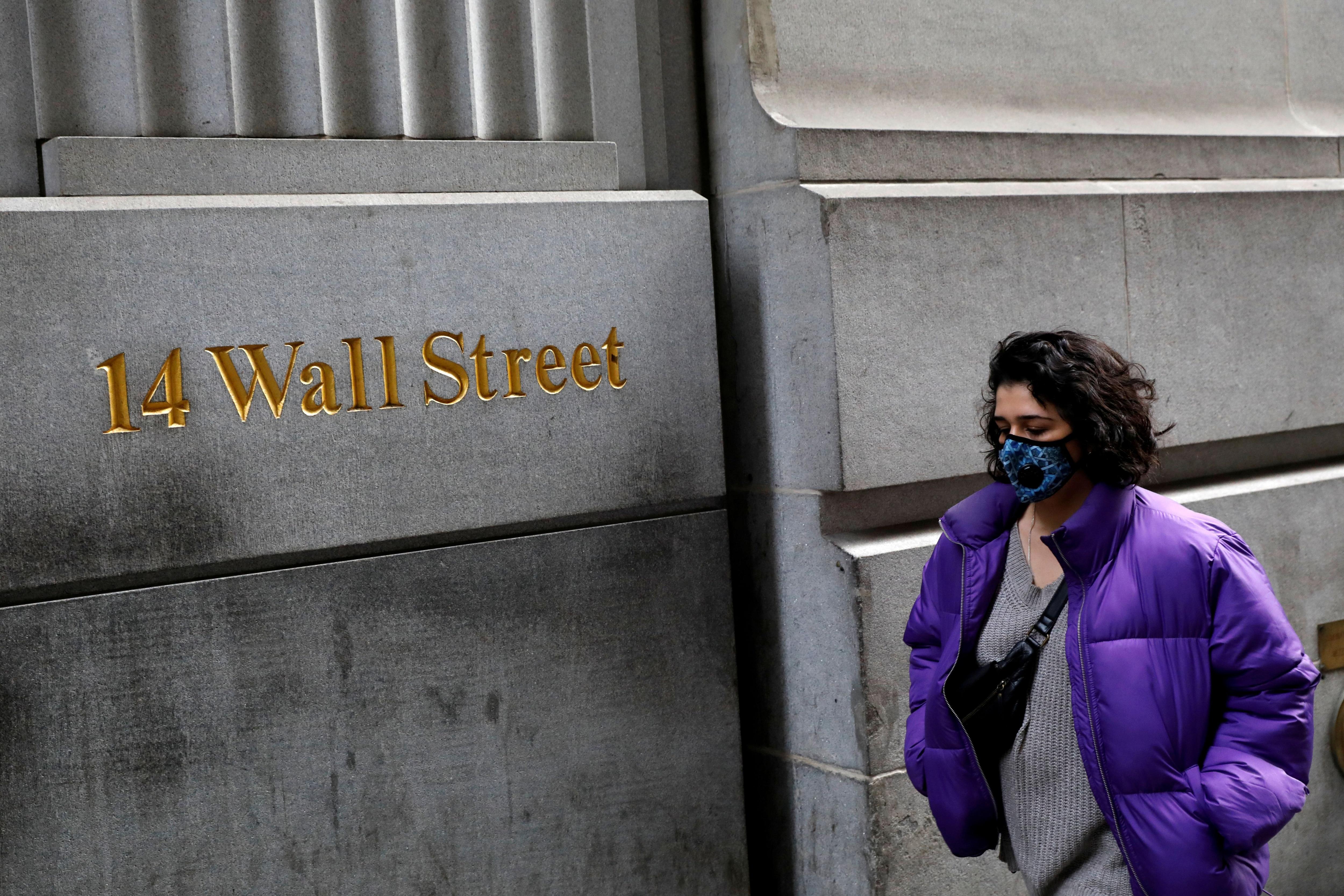 Una mujer con mascarilla camina por el distrito financiero de Nueva York (Reuters)