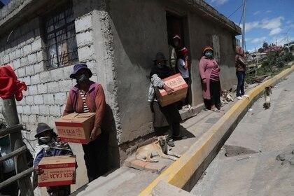 Vecinas con mascarilla sostienen cajas de alimentos distribuidas por el gobierno, durante una cuarentena para combatir la expansión del COVID-19 a las afueras de Quito, Ecuador, el miércoles 27 de mayo de 2020. (AP Foto/Dolores Ochoa)