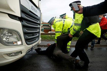 La policía arrastra una persona acostada en frente a su camión en el puerto de Dover (REUTERS/John Sibley)