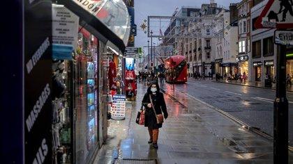 Una mujer camina por una calle húmeda por la lluvia en Oxford el primer día de restricciones de nivel 3 en Londres, el 16 de diciembre de 2020. (Andrew Testa/The New York Times)