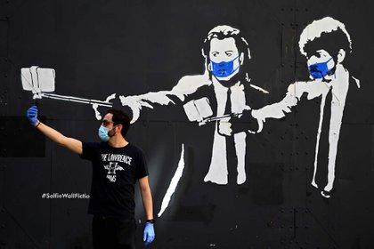 """Un hombre se toma una selfie junto a un stencil de los actores Samuel L. Jackson y John Travolta en la películas """"Pulp Fiction"""", adaptado e los tiempos de la pandemia, en una calle de Madrid, España."""