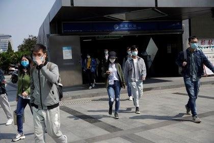 Personas con mascarillas salen de la estación de metro de Zhongguancun tras el brote de la enfermedad coronavirus (COVID-19), en Pekín, China, el 27 de abril de 2020. REUTERS/Tingshu Wang