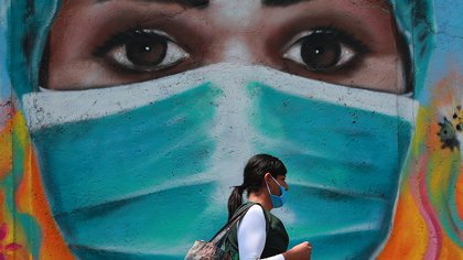 27/05/2020 dpatop - 27 May 2020, Mexico, Mexico City: A woman wearing a face mask walks next to a mural on the Mexico City streets, amid the Coronavirus (Covid-19) outbreak. Photo: Francisco Estrada/NOTIMEX/dpa