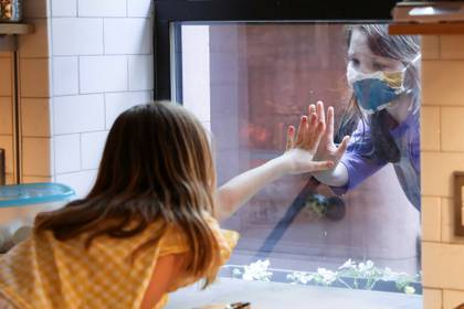 El saludo de dos amigas a través de una ventana en Brooklyn (Reuters)